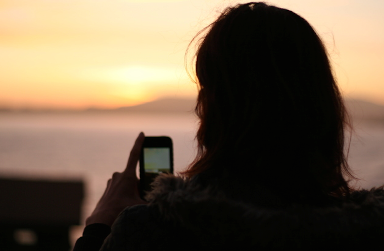 Girl with smartphone at sunset